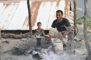25. Local blacksmith working on his furnace